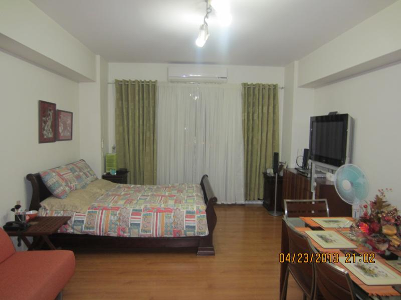 The bed, entertainment center, sliding door to the balcony - Cozy Condo for short-term rent in classy Alabang - Muntinlupa - rentals