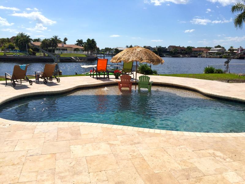 Back yard with new pool with beach and travertine decking. - GulfViews, Waterfront, Sunsets, Pool, Dock, Wirles - New Port Richey - rentals