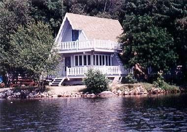 Summertime view of chalet with swimfloat and dock - Lakefront and mountainside 3 br chalet - Bridgton - rentals
