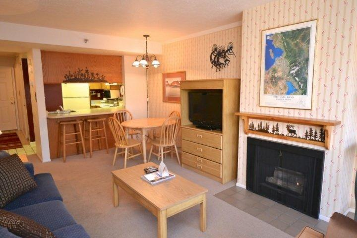 Living room is equipped with a gas fireplace, flat-screen TV and plush sofa. - Prospector Square New Claim - Park City - rentals