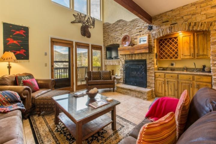 Stunning great room with a floor to ceiling wall of stone work with fireplace, large HDTV with Comcast TV and comfortable leather furnishings. - Aspenwood at Deer Valley - Park City - rentals