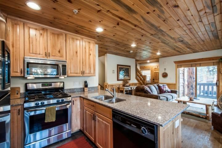 The open gourmet kitchen features hardwood cabinetry, recessed lighting, granite counter top and stainless steel appliances. - Timber Wolf 2 Bedroom at Canyons - Park City - rentals