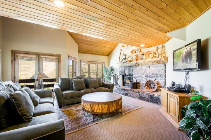 The living room is equipped two (2) plush couches that surround wood-burning fireplace with floor to ceiling stonework and the entertainment center. - Mountainside Park City Silver King 1197 Lowell Avenue - Park City - rentals