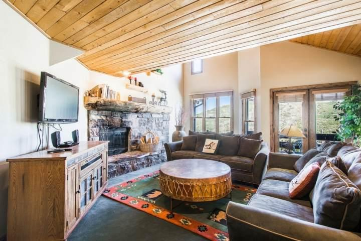 The living room is equipped with two (2) plush couches that surround a wood-burning fireplace with stonework and the entertainment center. - Mountainside Park City Silver Queen 1195 Lowell Avenue - Park City - rentals