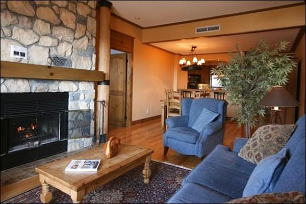 The Cozy Living Area Features a Flat Screen TV and a Beautiful Stone Fireplace - Incredible Lake and Mountain Views - Cozy Furnishings and Decor (6067) - Mont Tremblant - rentals