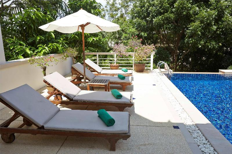 Sun loungers settle beside pool among natural trees. - Family pool villa walk to beach - Phuket (3BDR) - Karon - rentals