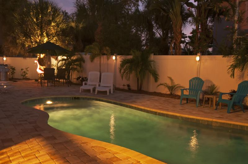 Outdoor pool area features lounge furniture, a BBQ, and a heated pool. - The PINK FLAMINGO—Best Location—Walk To The Beach! - Siesta Key - rentals
