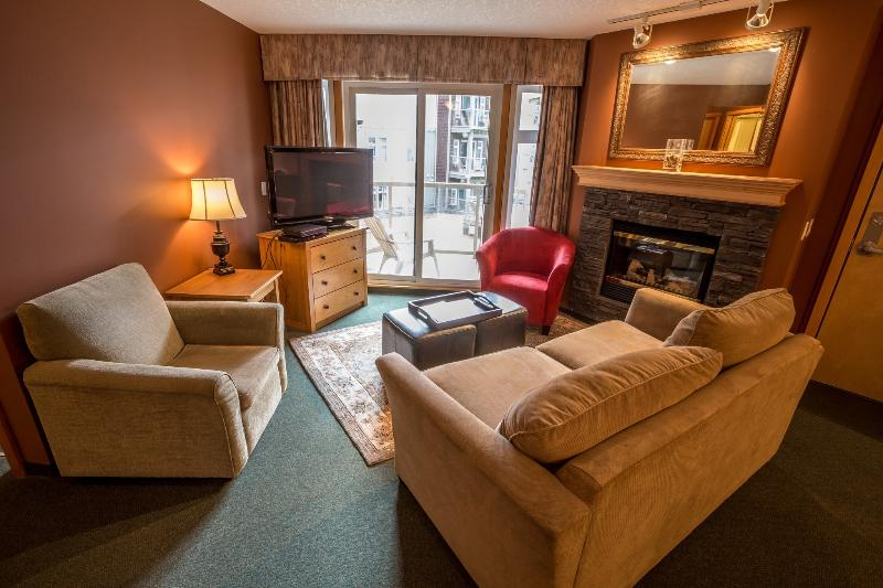Comfortable, cozy living area with fireplace and patio doors with deck access! - Canmore Windtower Lodge 2 Bedroom Fully-Equipped Condo - Canmore - rentals