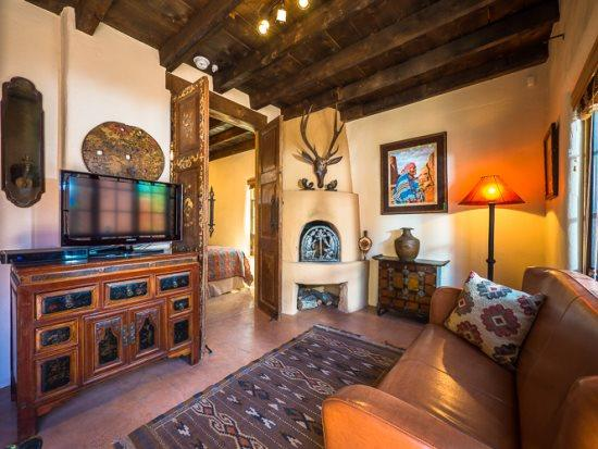 Living room with flat screen TV and kiva fireplace - Two Casitas-Desert Sky-Sweet Retreat Across from Santa Fe River Trail - Santa Fe - rentals
