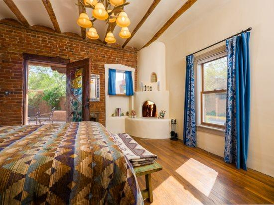 Bonita- bedroom with queen bed, working, kiva fireplace, and private patio - Two Casitas- Bonita - Adobe Home in the Heart of the Railyard - Santa Fe - rentals