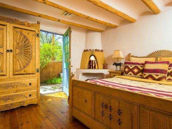 First bedroom featuring queen bed, working, kiva fireplace, and flat screen TV - Two Casitas - Mariposa Old Santa Fe Charm, Hot Tub - Santa Fe - rentals