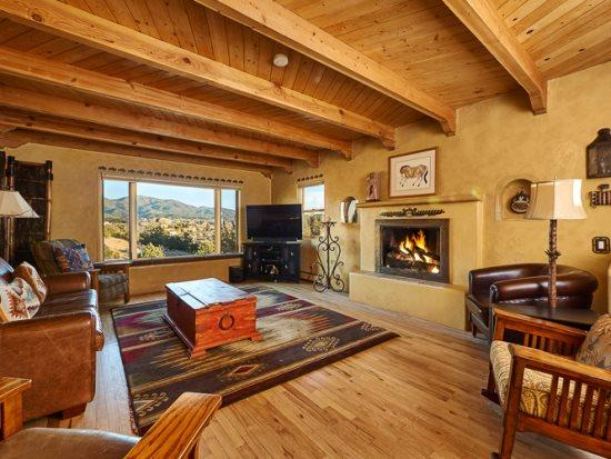 Northern wing living area with working fireplace, flat screen TV, and sleeper sofa - Two Casitas - Pinon Vista - 360 Majestic Views and Just Blocks from the Plaza! - Santa Fe - rentals