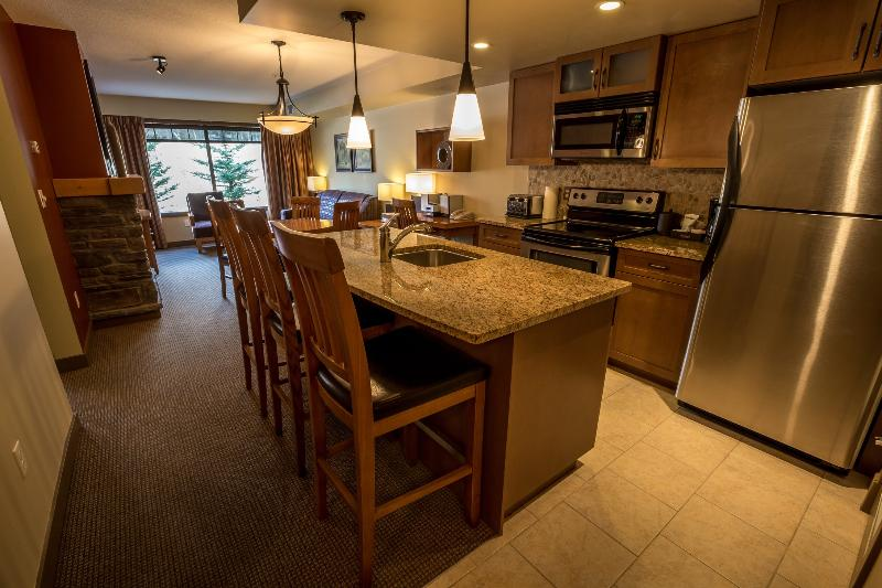The open-plan kitchen features stainless steel appliances and a breakfast bar - Copperstone Resort 1 Bedroom + Den Condo Near Canmore - Dead Man's Flats - rentals