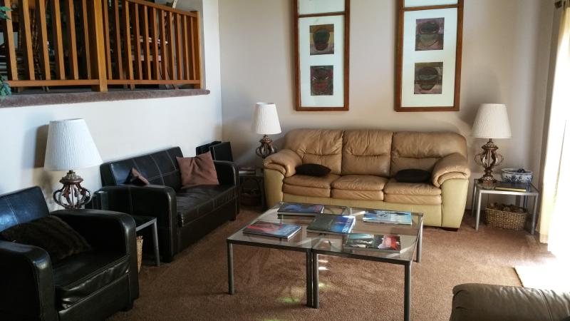 Living room: seats 10, cathedral ceiling, ceiling fan, tv/cable, bookshelf w/books, access to deck - Spacious Brigantine townhome, 3 blocks to beach - Brigantine - rentals