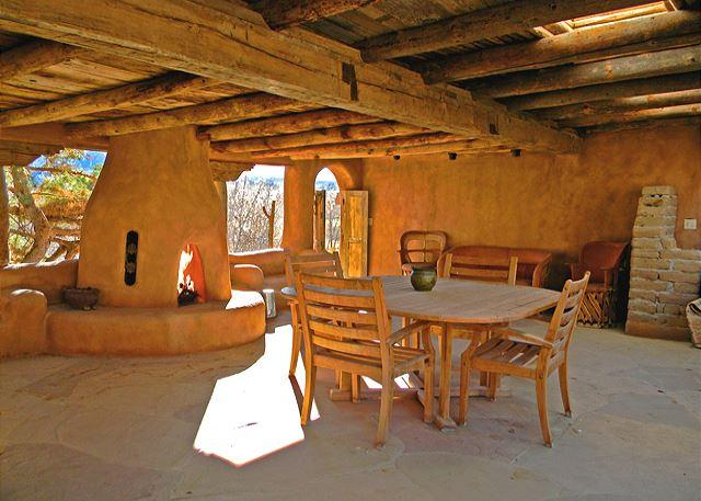 Extra large portal (covered patio in Spanish) with one of 5 kiva fireplaces, hot tub on lower terrace below  - Adobe Hacienda Main House Historic (1790) 5 miles south of Taos Plaza. - Ranchos De Taos - rentals