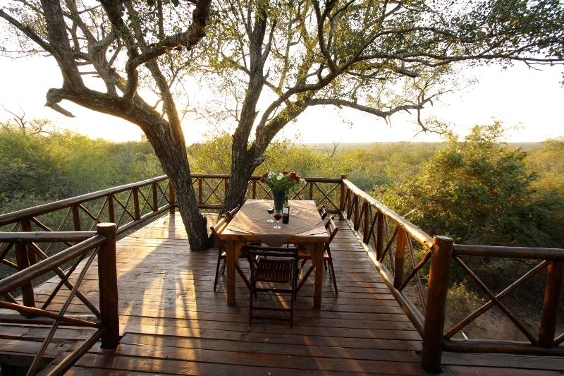 Outdoor eating on the deck surrounding a tree - Majuli Treehouse in Marloth Park beside Kruger - Marloth Park - rentals
