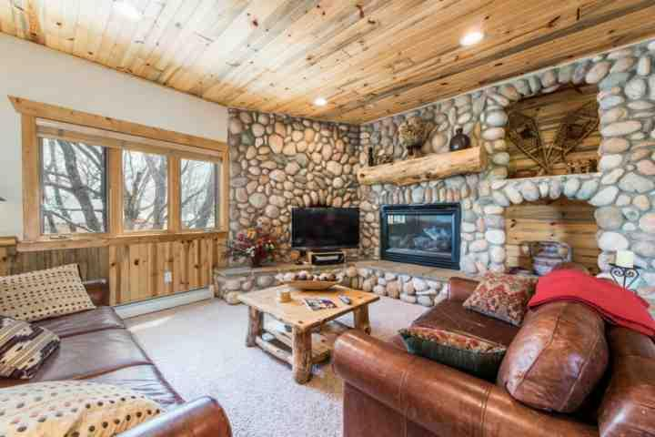 The living room is equipped with a large HDTV, comfortable leather sofa and matching loveseat, gas fireplace and river rock detailing. - Timber Wolf 2 Bedroom at Canyons 8C - Park City - rentals