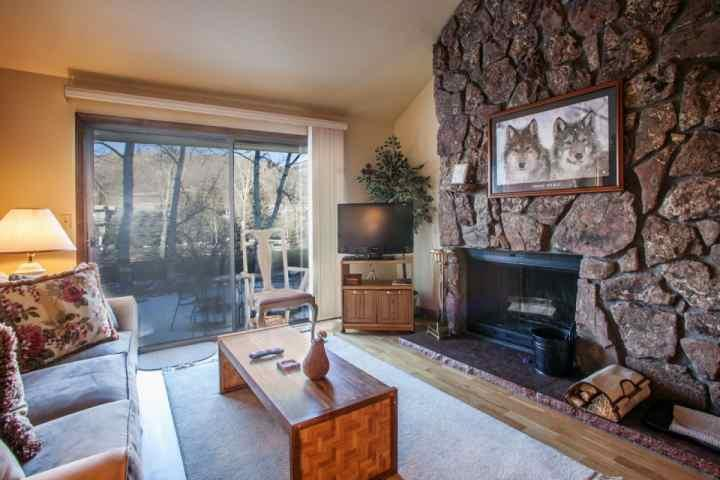Relax by the wood burning fireplace in this cozy living room with flat screen TV/DVD, family games and patio access. - Family Friendly Townhome, Easy Access to Vail & Beaver Creek, Golf Course - Eagle-Vail - rentals