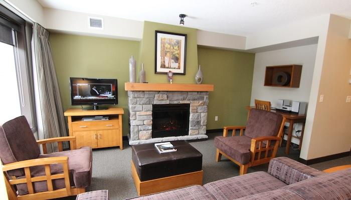This spacious living area is features a cozy fireplace, a flat-screen TV and a DVD player - Copperstone Resort 2 Bedroom + Den Condo Near Canmore - Dead Man's Flats - rentals