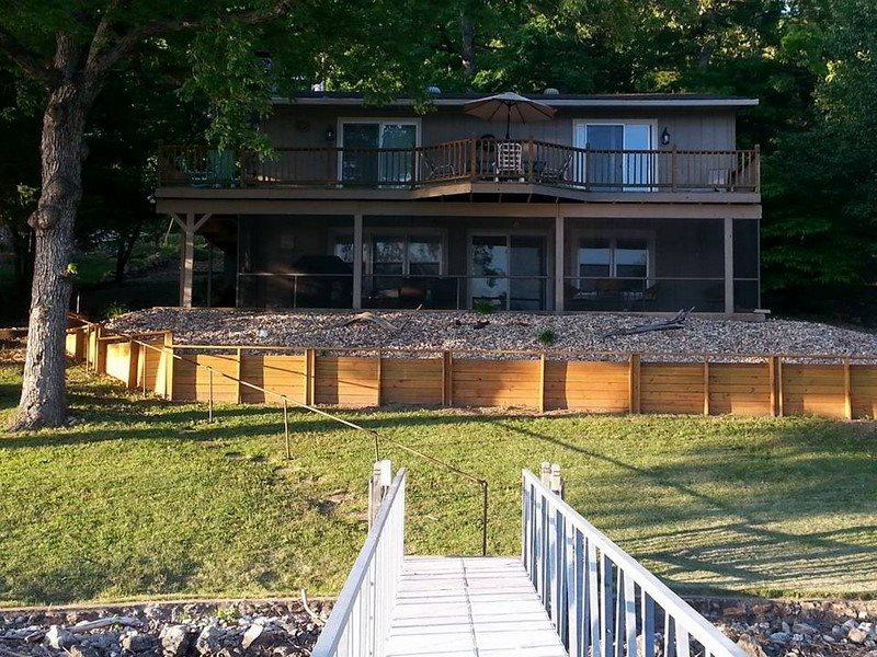 Lakeside of home, with grassy yard, screened in porch and shaded upper deck - Sunset Cove - Quaint Lake Home, Great Lake Views, No Wake Cove. 36 MM Osage Arm. - Sunrise Beach - rentals