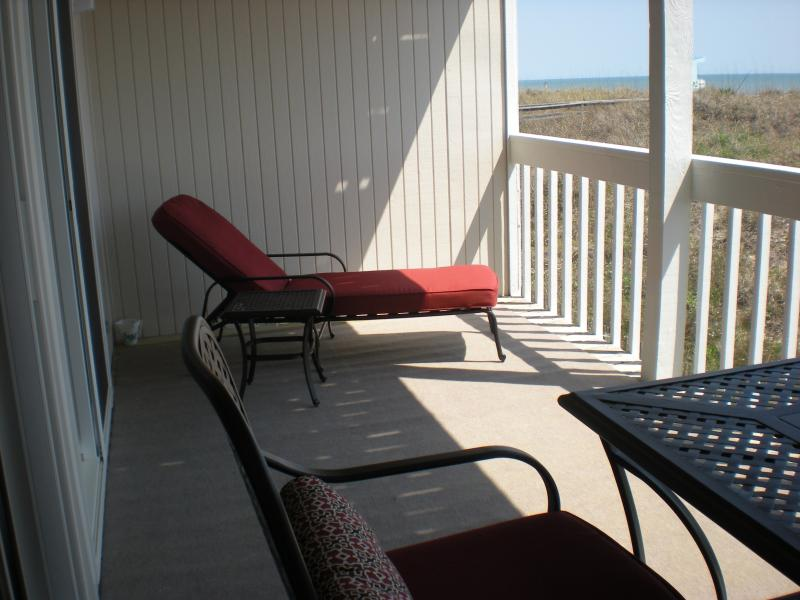 Chaise lounge and table on carpeted balcony deck - Oceanfront 2 Bedroom Condo - Carolina Beach - rentals