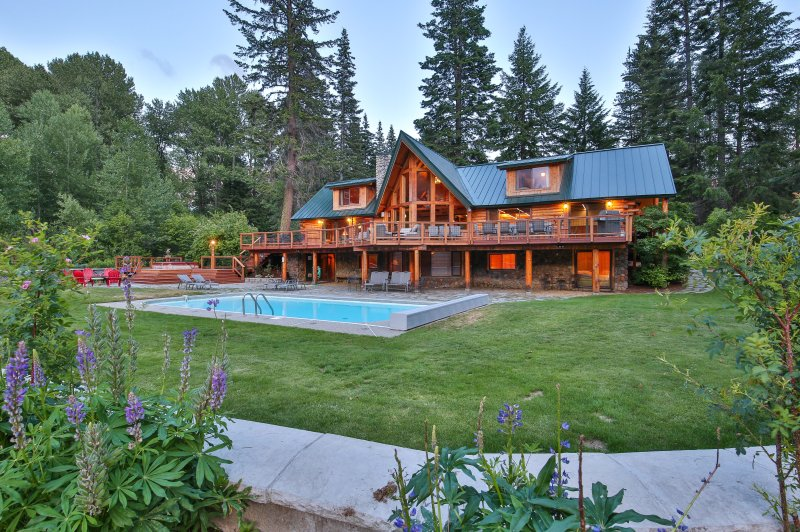 The Lodge viewed from back yard in summer, expansive deck with pool, hot tub - Heaven Can Wait   Private Riverfront Lodge - Plain - rentals