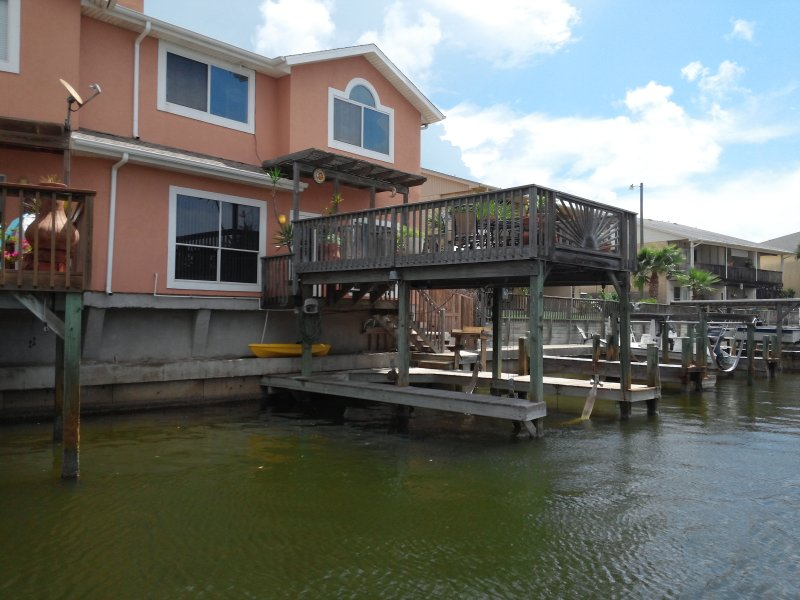 The back side to unit, with high deck, fish cleaner, swim ladder, boat lift/sling and dock, - The #1 Property - Late Summer Vacation Specials - Corpus Christi - rentals