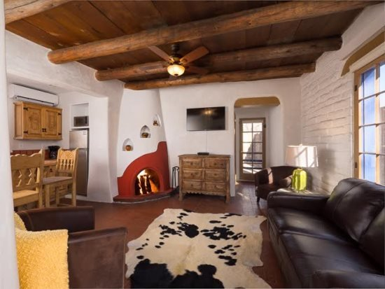 Besos- charming Eastside casita. Living room with working, kiva fireplace, sleeper sofa, and TV - Two Casitas - Besos - Romantic East Side Casita right off of Canyon Road - Santa Fe - rentals