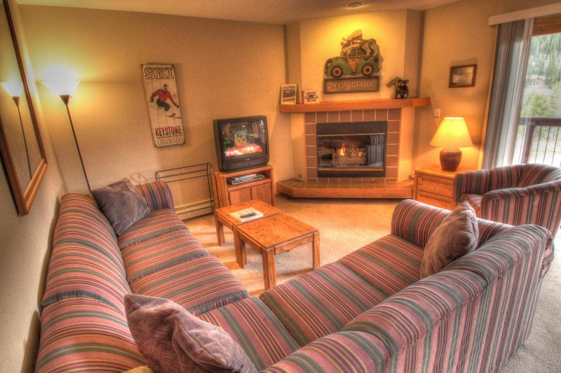 "SkyRun Property - ""C213 Cinnamon Ridge"" - Living Room - The living room has a gas burning fireplace and a TV. - C213 Cinnamon Ridge - Keystone - rentals"
