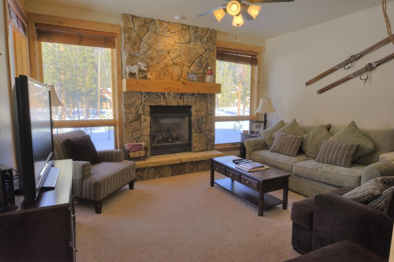 "SkyRun Property - ""6506 Settlers Creek Townhomes"" - Living Room - The living room features a natural stone fireplace and a flat screen TV. - 6506 Settlers Creek Townhomes - Keystone - rentals"