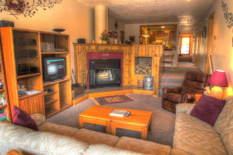 "SkyRun Property - ""2062 The Pines"" - Living Room - The recessed living room has a real wood burning fireplace with free wood delivered to your room. - 2062 The Pines - Keystone - rentals"