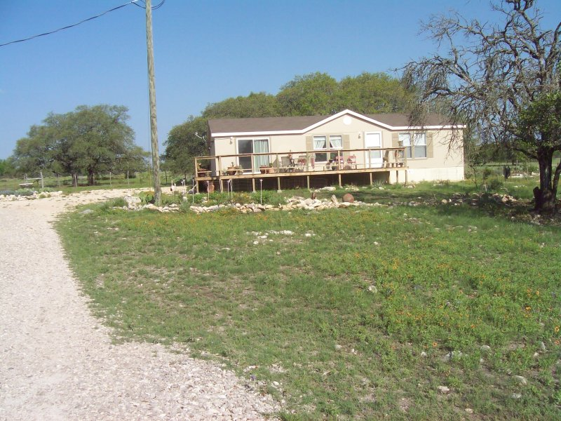 Front view of house backing up to 27 acres.  Gardens have actually matured. - Hill Country Getaway - Fredericksburg - rentals