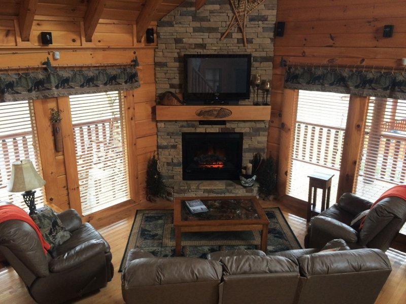 Leather furniture with 4 recliners. Hand carved mantle on stack stone fireplace - Happy Trails II Log Cabin in Bear Creek Crossing - Pigeon Forge - rentals