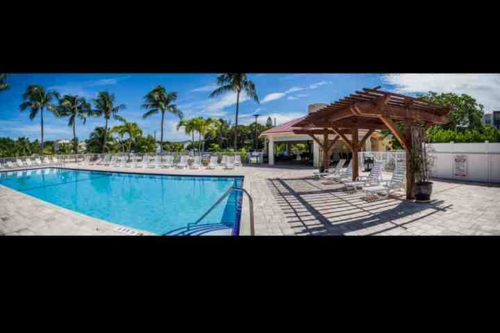 Panoramic view of the tropical pool, tiki hut and deck - Spacious Condo in the Tropical Futura Yacht Club; Free Parking for your Boat - Tavernier - rentals