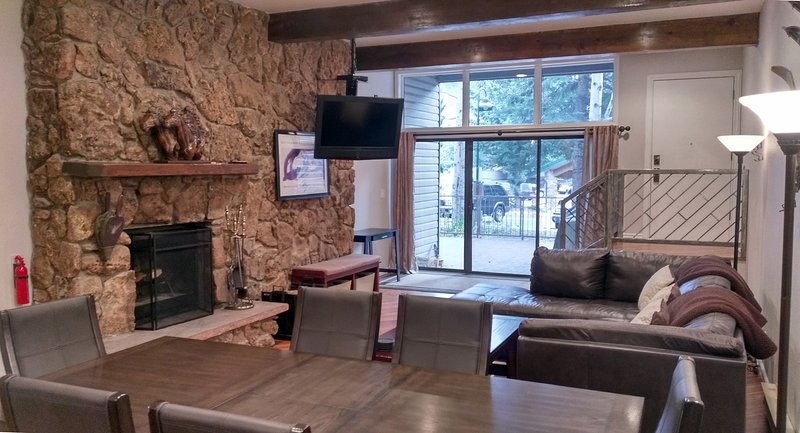 Living room with sofa bed, dining table, wood fireplace, and patio with gas BBQ - BC West 6 w/ FREE Skier Shuttle - Avon - rentals