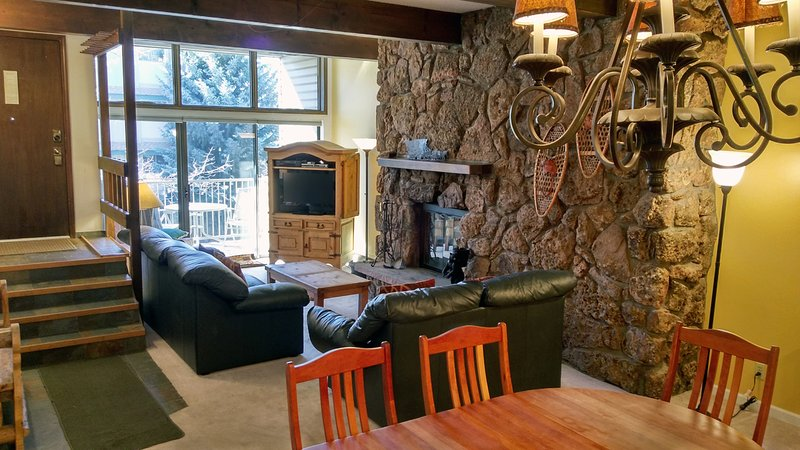 Living room with sofa bed, wood fireplace, dining table, and balcony w/ gas BBQ - BC West 19 w/ FREE Skier Shuttle - Avon - rentals