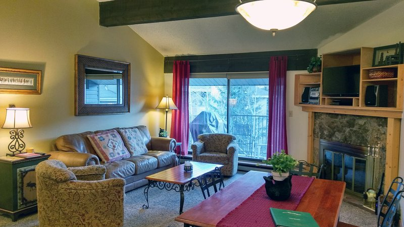 BC West Condo I-4 living room w/ sofa bed, wood fireplace, dining table, and balcony w/ gas BBQ - BC West I-4 w/ FREE Skier Shuttle - Avon - rentals