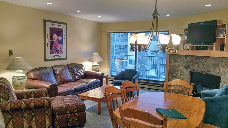 Living room with sofa bed, gas fireplace, dining table, and balcony w/ gas BBQ - BC West O-3 w/ FREE Skier Shuttle - Avon - rentals