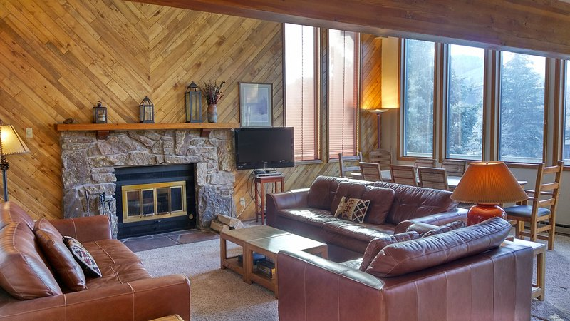 Living room with wood fireplace and dining table - 4-Bedroom Avon Townhouse w/ Private Garage & Sauna - Avon - rentals