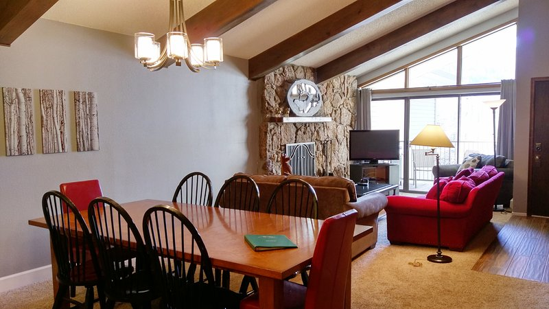 Beaver Creek West Condo #24 living room with wood fireplace, dining table, and balcony w/ gas BBQ - BC West 24 w/ FREE Skier Shuttle - Avon - rentals