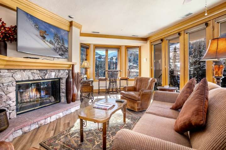 Living room with views of Strawberry Park, wood burning fireplace, large curved flat screen TV/Blu Ray DVD. - Beaver Creek Lodge Condo, Steps to Lifts, Shopping and Dining, Year Round Pool & Hot Tub! - Beaver Creek - rentals