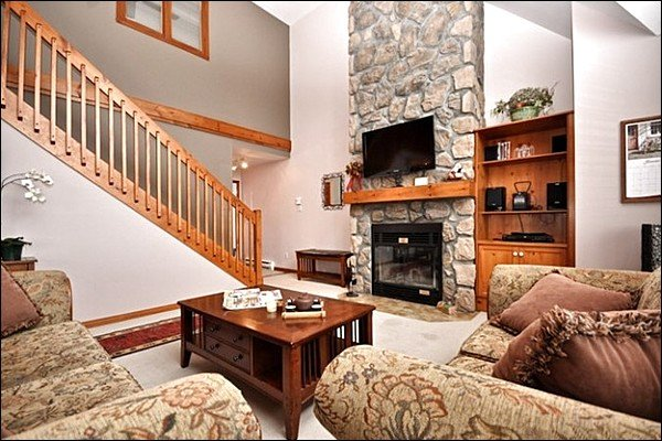The Living Area Features Large Picturesque Windows and a Cozy Stone Fireplace - Private Balcony with Summer BBQ - Common Area Summer Hot Tub and Swimming Pool (6113) - Mont Tremblant - rentals