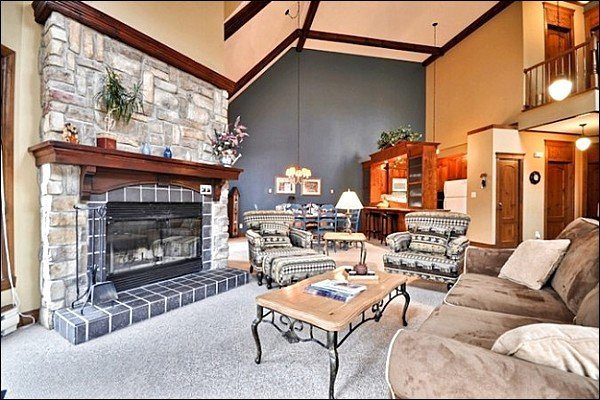 The Living Area Features a Beautiful Stone Fireplace, Large Picturesque Windows, and Cozy Furnishings - Common Area Golf Putting Green - Shared Summer Swimming Pool and Hot Tub (6126) - Mont Tremblant - rentals