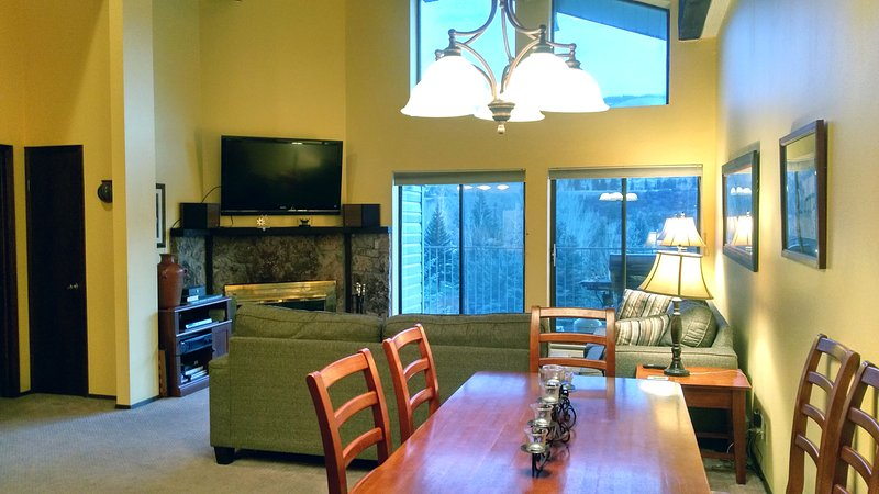 Beaver Creek West Condo Q-4 living room with wood fireplace, dining table, and balcony w/ gas BBQ - BC West Q-4 w/ FREE Skier Shuttle - Avon - rentals