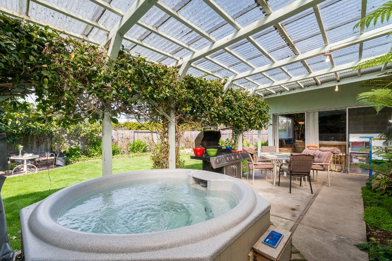 Covered patio with hot tub, gas grill, patio table and grassy fenced-in yard with room to play. - Kate's Cottage by the Sea: A Family Retreat in Santa Cruz, CA.  Walk to Beach! - Santa Cruz - rentals