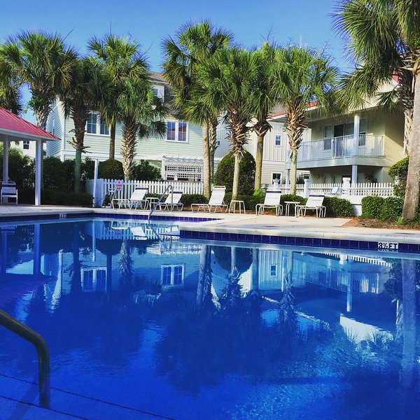 Large pool surrounded by palm trees - plenty of seating around pool deck at Sugar Sand Sea-esta - The Charm of Seagrove - Beautiful 2 Bedroom 2 Bath - Santa Rosa Beach - rentals
