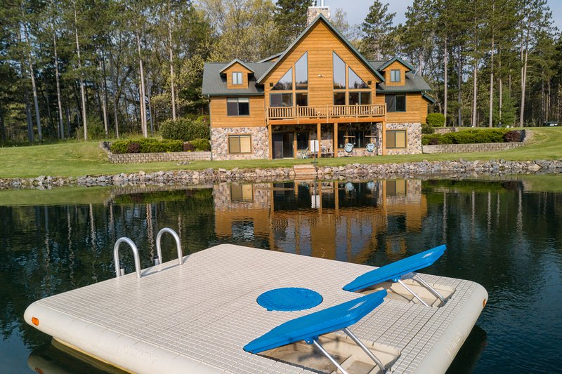 view of the home from the Otter Island Swim raft - Spacious Retreat with Private Swimming/Fishing Pond and Sand Volleyball Court - Wisconsin Dells - rentals