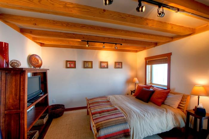 The cozy bedroom has a queen sized bed and a timbered ceiling. - Timber Framed Cabin w/ Gorgeous Mountain Views! - Bozeman - rentals