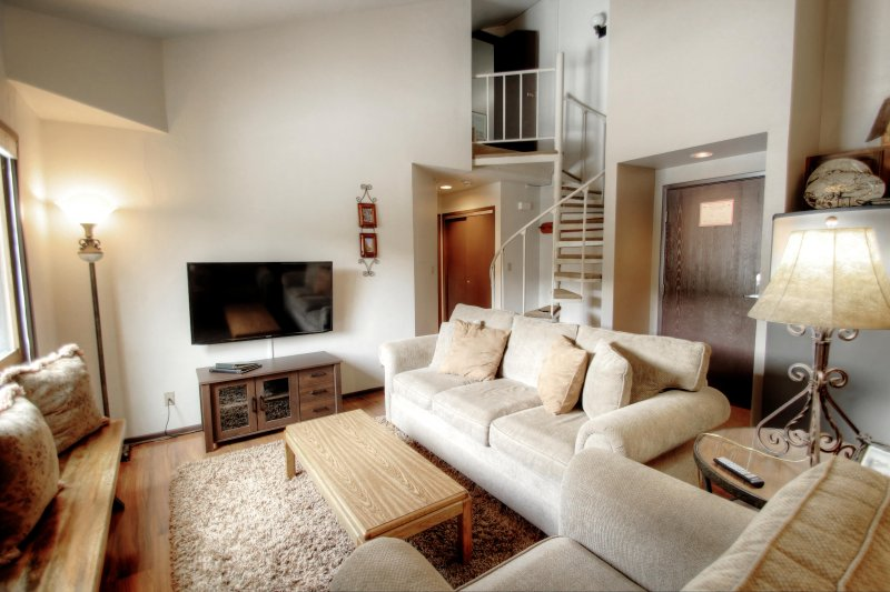 """SkyRun Property - """"1168 Flying Dutchman"""" - Living Room - The winding staircase pictured here leads to the loft style guest bedroom. - 1168 Flying Dutchman - Keystone - rentals"""