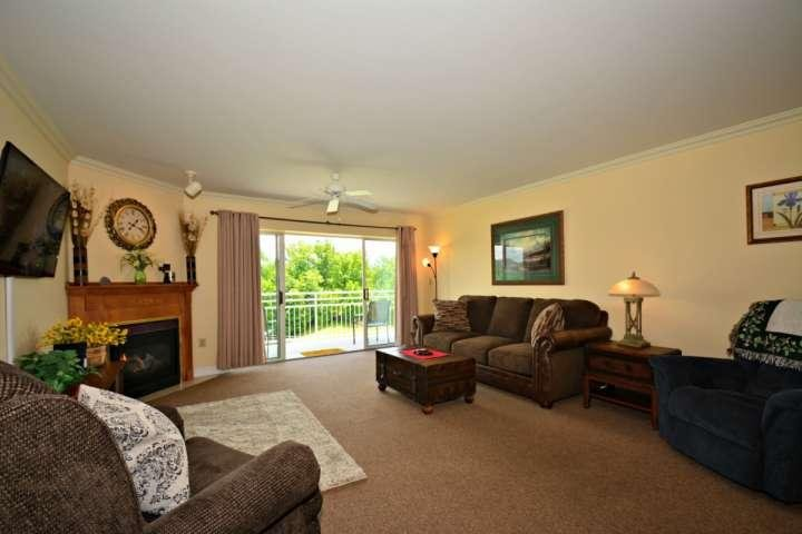 Living room features plenty of plush furnishings, as well as a fireplace, flatscreen tv, and balcony access! - Golf Vista 162 - Luxurious 2BR/2BA Condo~ Located in the Heart of Pigeon Forge - Pigeon Forge - rentals